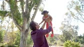 throw away : Father throwing his young daughter in the air in a park