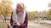 britânico : British Muslim Woman Texting On Mobile Phone In Park