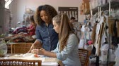 sentar se : Woman stands to train an apprentice at clothes design studio Stock Footage