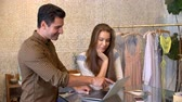 бутик : Male manager and female trainee using laptop in clothes shop