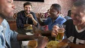 four people : Group Of Male Friends Eating Out In Sports Bar Shot On R3D Stock Footage