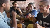 hambúrguer : Group Of Male Friends Eating Out In Sports Bar Shot On R3D Vídeos