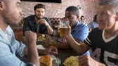 hambúrguer : Group Of Male Friends Eating Out In Sports Bar Shot On R3D Stock Footage
