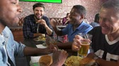 forties : Group Of Male Friends Eating Out In Sports Bar Shot On R3D Stock Footage