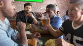 elliler : Group Of Male Friends Eating Out In Sports Bar Shot On R3D Stok Video