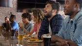 ponto : Group Of Friends Watching Game In Sports Bar On Screens