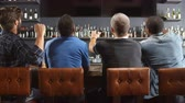 ponto : Rear View Of Male Friends Watching Game In Sports Bar