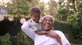 dede : Young black boy playing with grandad in the garden, close up