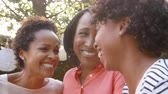 one person only : Black mother and adult daughters talking in garden, close up