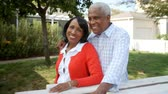 orgulho : Senior black couple walk into focus outside their home Stock Footage