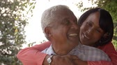 backyard : Senior black couple piggyback in garden, close up