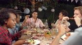 socialising : Young adult friends eat and drink at an outdoor dinner party Stock Footage
