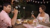 dospělí : Young black couple make a toast at dinner in a garden