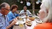 forties : Group Of Mature Friends Enjoying Outdoor Meal In Backyard