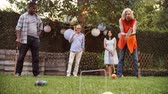 forties : Group Of Mature Friends Playing Croquet In Backyard Together Stock Footage