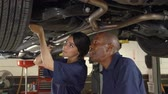 tekerlek : Mechanic And Female Trainee Working Underneath Car Together Stok Video