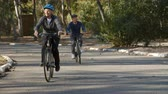 hetvenes évek : Senior Couple Cycling Through Park In Slow Motion