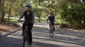lifestyle shot : Senior Couple Cycling Through Park In Slow Motion