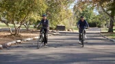 střední : Senior Couple Cycling Through Park In Slow Motion