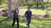 lifestyle shot : Senior Couple Power Walking Through Park In Slow Motion