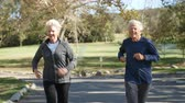 vista frontal : Senior Couple Exercising With Run Through Park Vídeos