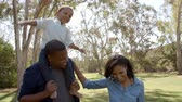 piggyback : Parents with son on dad�s shoulders having fun in the park Stock Footage