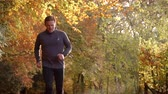 lifestyle shot : Mature Man Running Through Autumn Landscape In Slow Motion