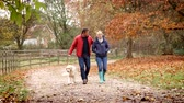 lifestyle shot : Mature Couple On Autumn Walk With Golden Retriever