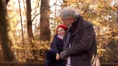 náklonnost : Granddaughter On Autumn Walk With Grandfather Sits On Fence