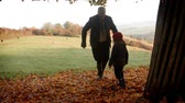 внучка : Grandfather And Granddaughter Kicking Leaves On Autumn Walk
