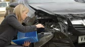 report : Female Loss Adjuster Writing Report On Damaged Car