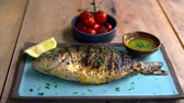 tempero : Chargrilled whole fish, roasted tomatoes and dressing, zoom Stock Footage