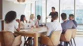 collaborating : Businesswoman Stands To Address Meeting Around Board Table Stock Footage