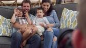 nevetés : Smiling Family Sit On Sofa At Home Having Photograph Taken