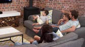 propriedade : Family Sit On Sofa In Open Plan Lounge Watching Television Stock Footage