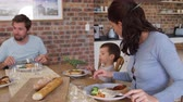 quatro pessoas : Family Eating Meal In Open Plan Kitchen Together Stock Footage