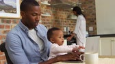 móveis : Father And Baby Daughter Use Laptop As Mother Prepares Meal