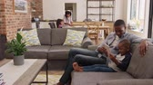 móveis : Father And Son Sit On Sofa In Lounge Using Digital Tablet Stock Footage