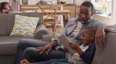 four people : Father And Son Sit On Sofa In Lounge Using Digital Tablet Stock Footage