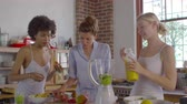 olhando para baixo : Three female friends making smoothies together in kitchen, shot on R3D