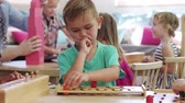 bloco : Montessori Pupil Working At Desk With Wooden Shape Puzzle