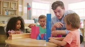 ilerleme : Teacher And Pupils Using Wooden Shapes In Montessori School Stok Video
