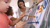 tuval : Teacher At Montessori School Helping Children in Art Class
