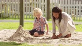 яма : Teacher At Montessori School Playing With Male Pupil In Sand Pit