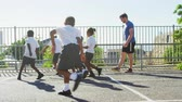 bolas : Teacher plays football with young kids in school playground Stock Footage