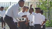 ventoso : Teacher holds ball and talks to school kids in playground