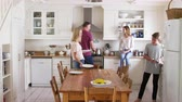 четыре человека : Family With Teenage Children Preparing Breakfast In Kitchen