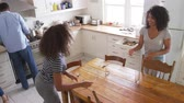 helpful : Family With Teenage Children Laying Table For Meal In Kitchen
