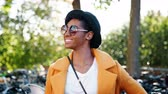 regno unito : Fashionable young black woman standing outdoors wearing sunglasses, a yellow coat and a black hat looking to camera and laughing, close up, focus on foreground