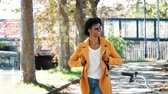 três pessoas : Fashionable young black woman wearing a hat, sunglasses, blue jeans and a yellow pea coat walking along a treelined city street on a sunny day, looking around, smiling, front view
